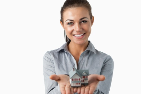 Female estate agent holding miniature house in her hands against a white background Stock Photo - 11624517