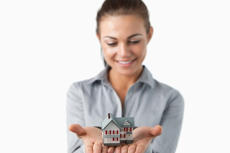 Miniature house being held by female estate agent against a white background Stock Photo - 11624242