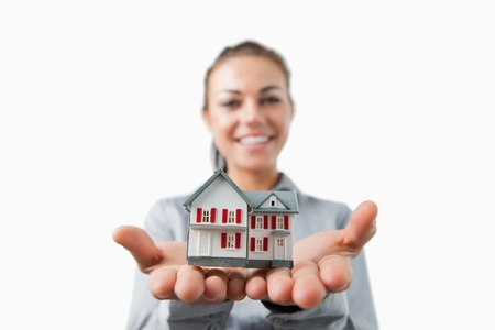 Miniature house being presented by female estate agent against a white background Stock Photo - 11623855