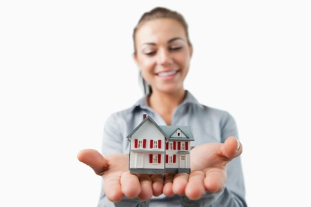 Miniature house being held by young female estate agent against a white background Stock Photo - 11624000