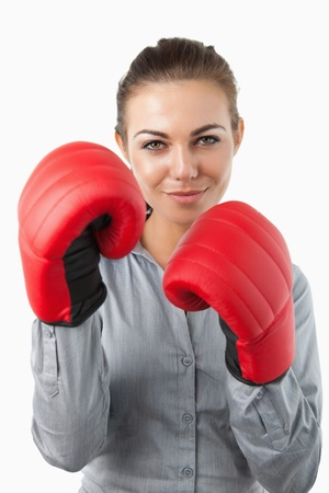 Businesswoman with boxing gloves against a white background photo