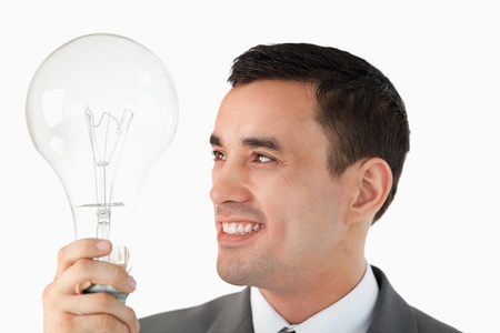 Close up of businessman with huge light bulb against a white background Stock Photo - 11637043