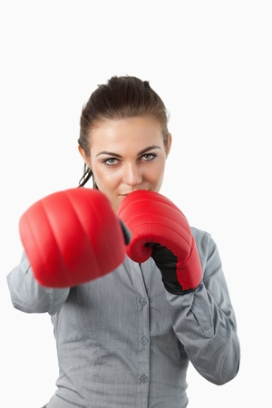 Businesswoman with boxing gloves slamming against a white background photo