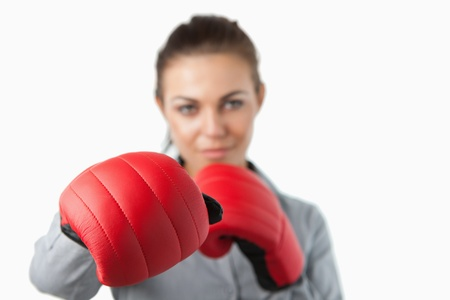 Boxing gloves used to slam by young businesswoman against a white background photo