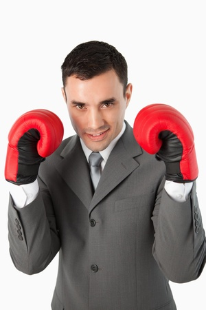 Close up of smiling businessman with boxing gloves on against a white background photo