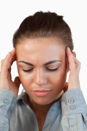 Close up of businesswoman suffering from a headache against a white background photo