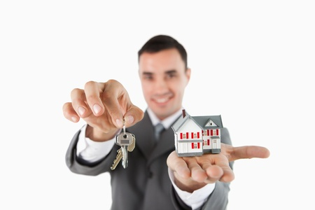 Close up of keys and miniature house being held by male estate agent against a white background photo