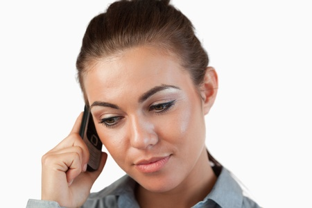 Close up of businesswoman listening closely to caller against a white background photo