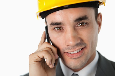 Close up of confident architect on the phone against a white background photo