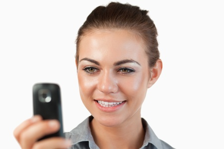 Close up of smiling businesswoman reading a text message against a white background photo