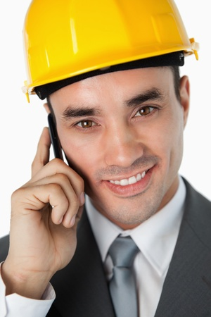 Close up of smiling architect talking on the phone against a white background photo
