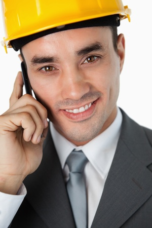 Close up of smiling architect listening to caller against a white background photo