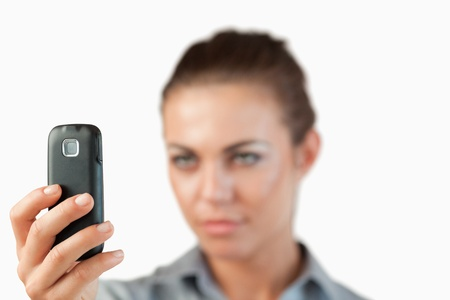 Close up of cellphone being held by businesswoman against a white background photo