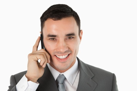 Close up of friendly businessman on the phone against a white background photo
