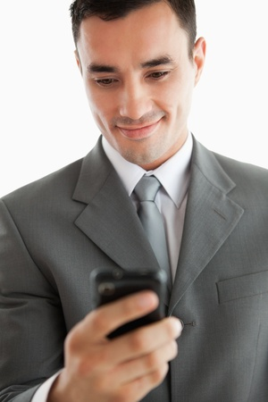Close up of businessman writing text message on his phone against a white background photo