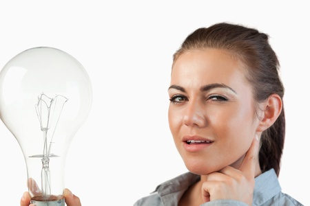 Businesswoman with huge light bulb against a white background photo