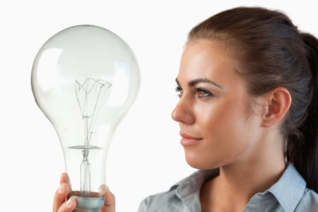 Businesswoman looking at huge light bulb in her hands against a white background photo
