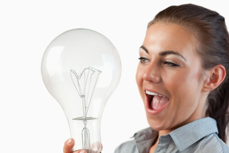 Close up of businesswoman being surprised by huge light bulb against a white background photo