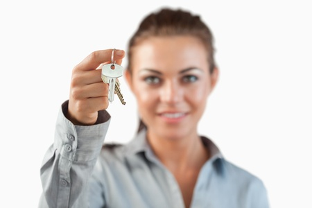 Close up of keys being held by female estate agent against a white background photo