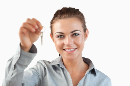 Close up of female estate agent holding keys against a white background photo