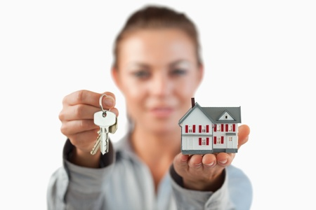 Miniature house and keys being presented by female estate agent against a white background photo