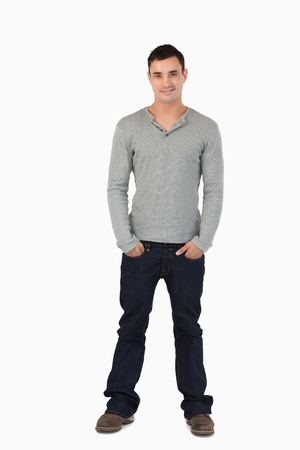 Young male with hands in his pocket against a white background