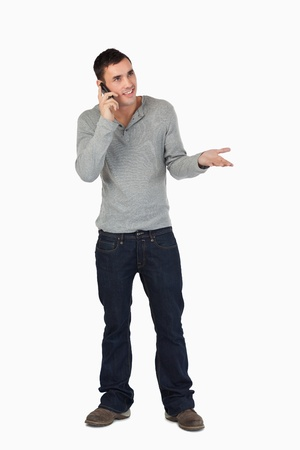 Young male gesturing while on the phone against a white background photo