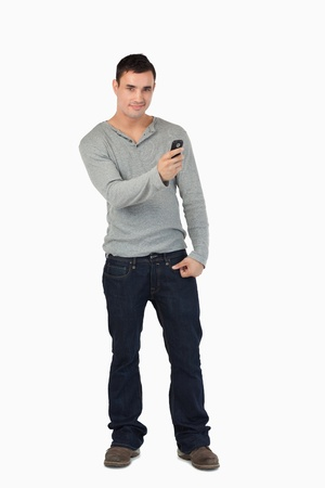 Young male writing text message while standing against a white background photo