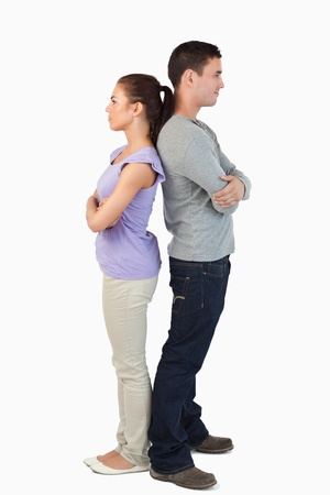 Young couple standing back-to-back against a white background photo