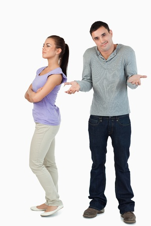 clue: Young male has no clue why his girlfriend is upset against a white background Stock Photo