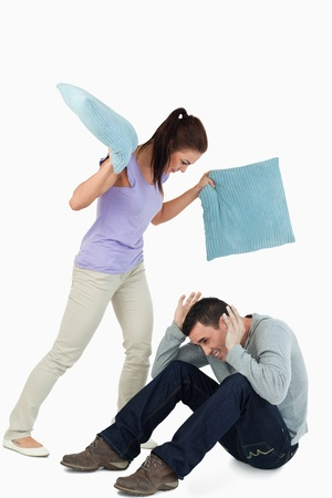 Young female hitting her boyfriend with pillows against a white background photo