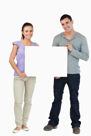 blank poster: Young couple holding sign against a white background Stock Photo