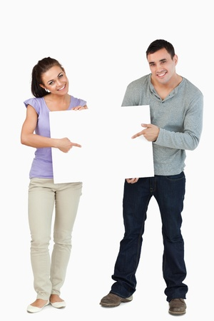 Smiling young couple holding sign together against a white background photo