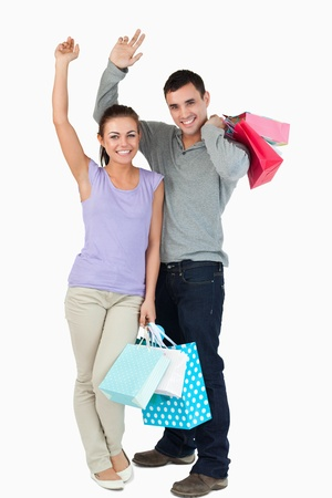 purchasing: Happy young couple after shopping against a white background