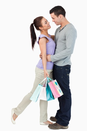 Young couple hugging during shopping tour against a white background photo