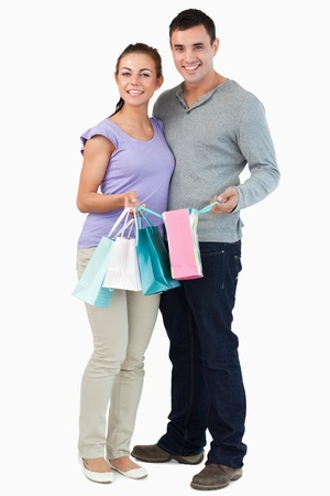 Young couple with their shopping against a white background photo