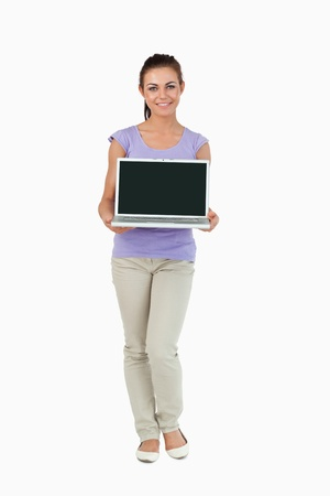 Smiling young female presenting her laptop screen against a white background photo