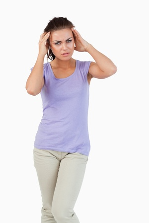 experiencing: Young female experiencing a headache against a white background Stock Photo