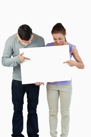 Young couple pointing at banner they are holding against a white background photo