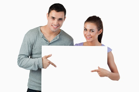 Young couple pointing at banner in front of them against a white background photo