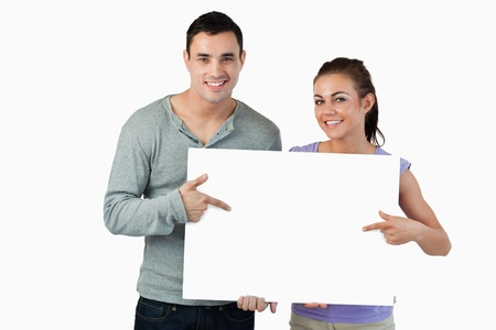 Smiling young couple pointing at sign they are holding against a white background photo