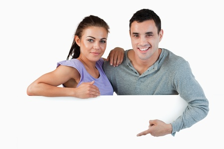 Young couple presenting advertisement against a white background photo
