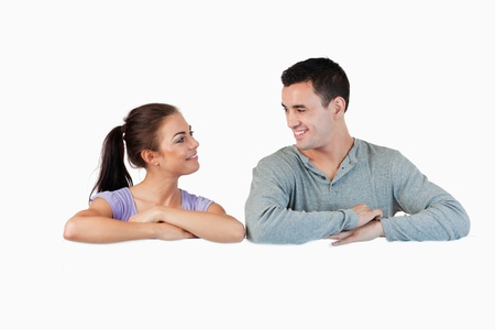 Young couple looking at each other while leaning on a wall against a white background photo