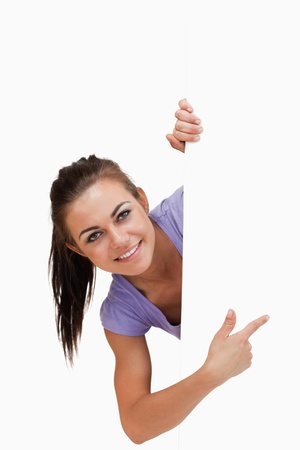 Smiling young female pointing around the corner against a white background photo