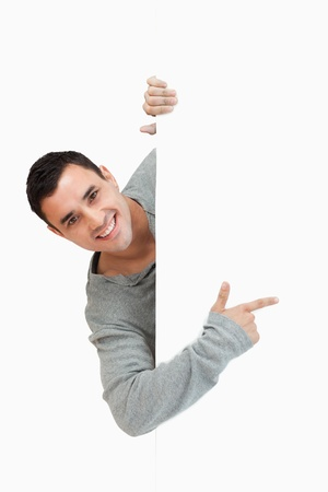 looking behind: Smiling young male pointing around the corner against a white background Stock Photo