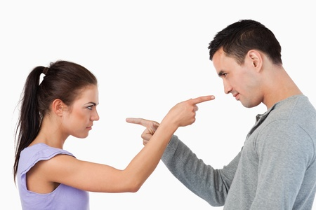 Young couple pointing at each other against a white background photo