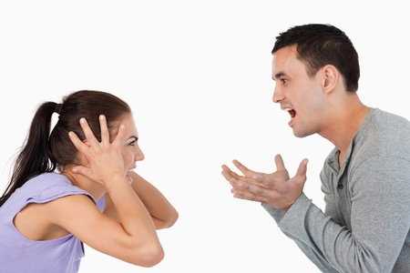 Young couple yelling at each other against a white background photo