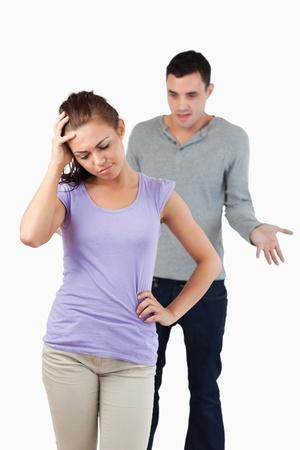 pareja discutiendo: Mujer joven decepcionado con su novio sobre un fondo blanco Foto de archivo
