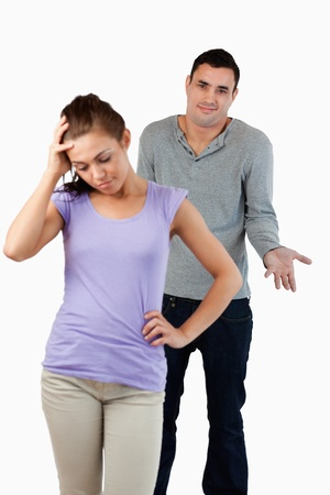 Young male has no clue how to calm his girlfriend against a white background photo