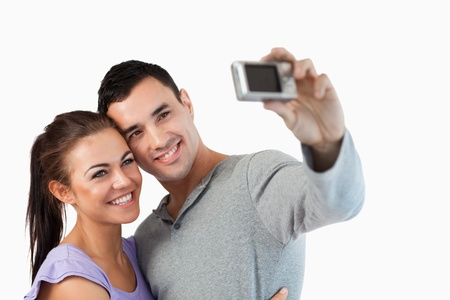 Young couple taking a picture of themselves against a white background photo